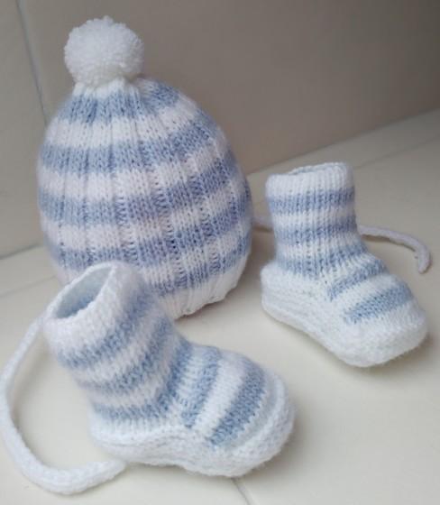 Первый раз связала шапочку с ушками и носочки в форме ботиночек ну или что-то похожее на них .